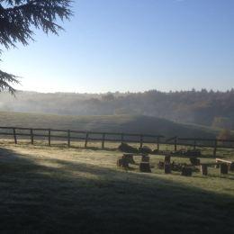 Grasveld met vuurplaats aan de voorzijde van het kasteel, met uitzicht op de vallei