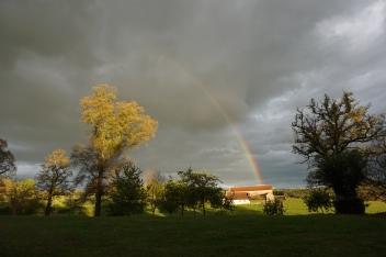 Regenboog boven de boerderij van de buren